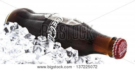 SWINDON UK - JANUARY 26 2014: Classic bottle of Coca-Cola on a bed of ice over a white background