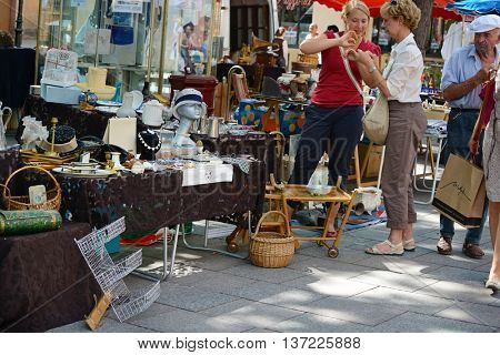 Strasbourg, France - July, 2012: Two unidentified women make a purchase at a flea market near the city center. Editorial only.