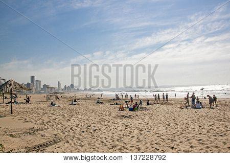 People On Addington Beach Against City Skyline