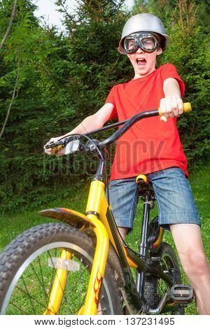 Cute teen boy wearing metal cauldron as a helmet and goggles posing on a bicycle in a summer park - a funny power cyclist concept