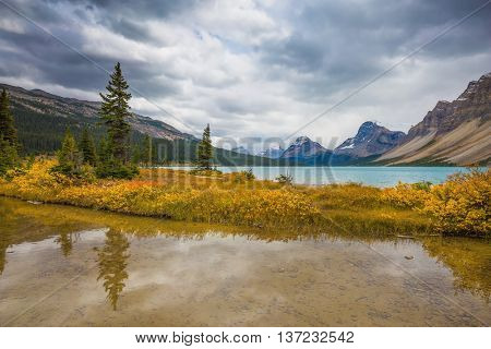 Banff National Park. The smooth water reflects the cloudy sky. Snow-capped mountains and glaciers surroundings Bow Lake