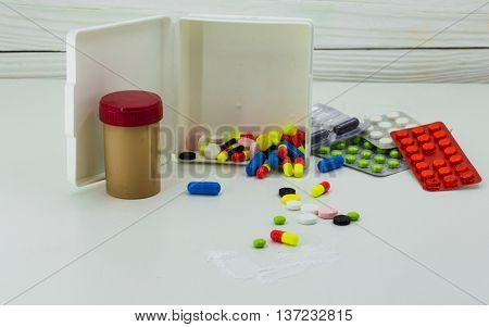 Medicine pills of different colors on a white background drugs