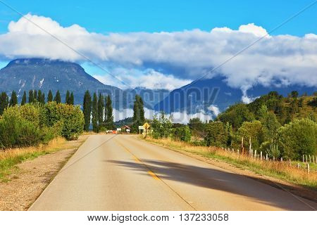 Countryside in Chilean Patagonia. Broad highway leading to the picturesque village. Mountain range is visible in the distance