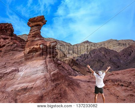 Unique  outcrops  in the mountains of pink sandstone. A lone tourist threw his hands up in delight in Eilat Mountains