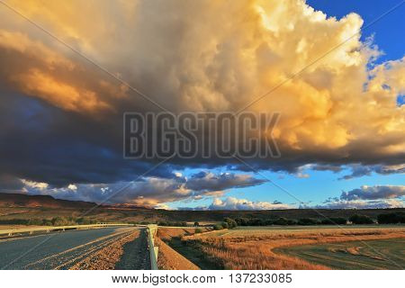 Storm over the Pampas.  In the steppe runs a gravel road. The enormous storm cloud and a flat plain covered in orange sunset.