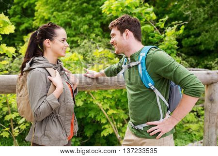 travel, hiking, backpacking, tourism and people concept - smiling couple with backpacks in nature