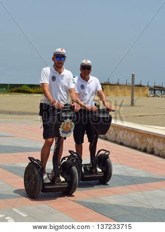 Torremolinos, Andalucia, Spain - June 27, 2016: Policemen on duty patrolling seafront promenade on Segways.