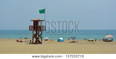 Torremolinos, Andalucia, Spain - June 27, 2016: Torremolinos Beach with holiday makers and watch tower with green flag.