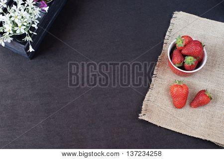 Fresh Strawberries In Mini Metal Bucket On Hessian Jute. White And Purple Flowers In A Decorative Wo