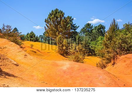 The  mining ocher quarry. Orange and red picturesque hills. Languedoc - Roussillon, Provence, France
