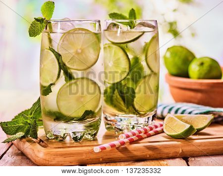 Alcohol drink. On wooden boards two glasses with alcohol drink and ice cubes. A drink number thirty three cocktail mohito with straw and lime and mint leaf. Country life. Outdoor. Light background.