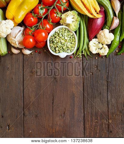 Green peas in a bowl with fresh vegetables on wood top view