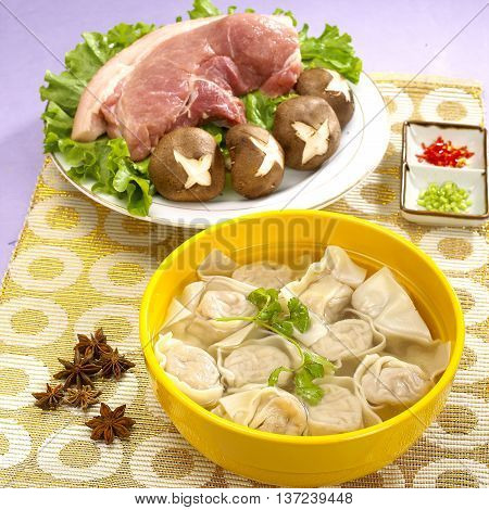 Traditional Chinese bowl of wanton noodle with pork and mushroom on the table
