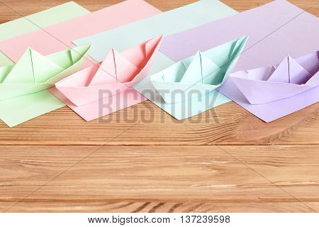 Pink, green, lilac, blue paper origami ships toys on wooden table with empty space for text. Colored paper sheets. Easy summer origami for kids. Hand crafts for children