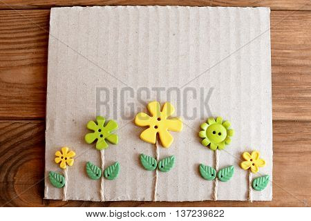 Greeting card with flowers. Card is made from cardboard box, plastic buttons, leaves and waxed cord. Wooden background with empty space for text