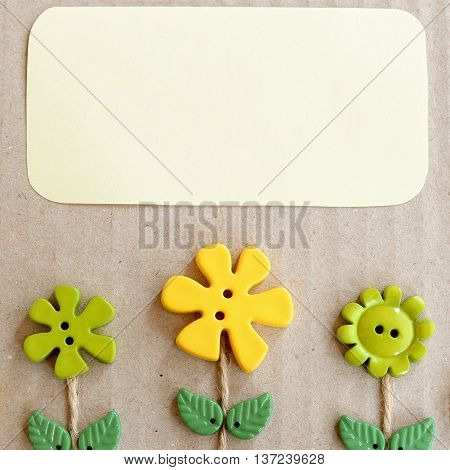Cardboard background with green and yellow plastic buttons flowers and leaves and empty copy space for text. Summer background