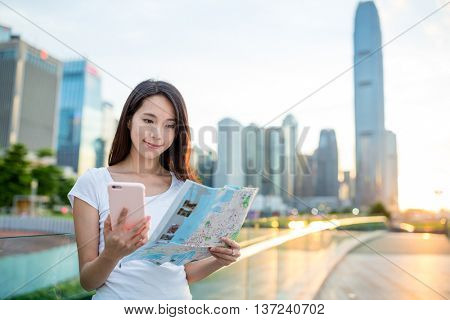 Young woman using city map and hold with cellphone