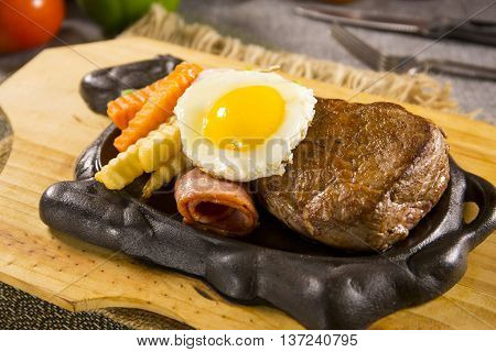Beefsteak on iron plate with egg and carrot on the table in restautrant