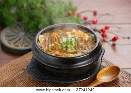 Chinese clams soup in black bowl on the table in restaurant