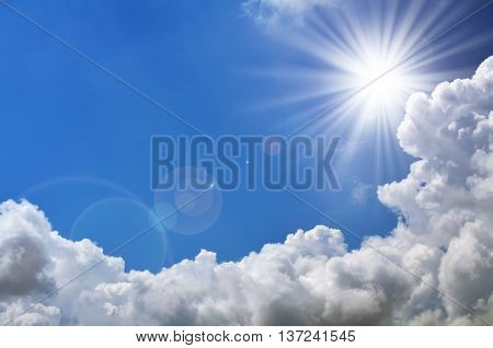 Bright sun shines among the dark clouds in the blue sky