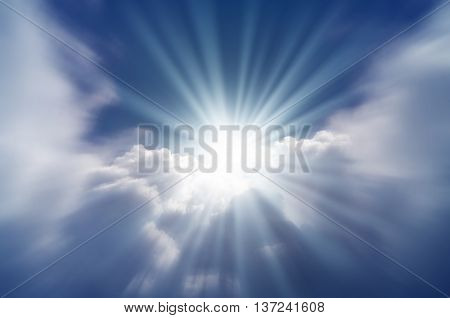 A bright flash of sun from behind the clouds on a background of blue sky