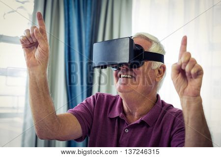 Senior man wearing virtual glasses at home
