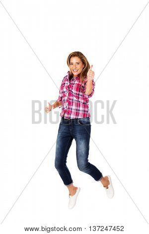 Happy young woman jumping giving thumbs up