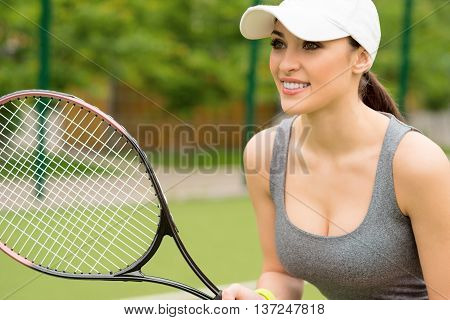 Ready to return a ball. Professional tennis player is standing and looking forward with anticipation. Woman is holding a racket and smiling