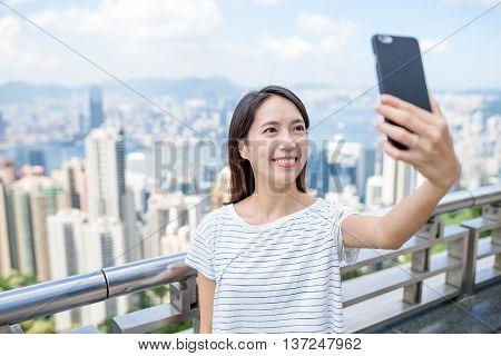 Woman taking selfie by mobile phone in Hong Kong