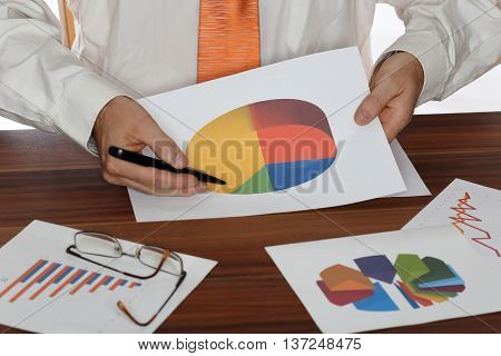 business man shows different diagrams on desk