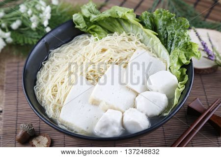 Traditional chinese bowl of wanton vermicelli with fish ball and paste on the table in restaurant
