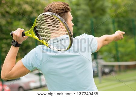 I am ready to beat the ball. Professional tennis player is raising the racket behind his head. Man is holding a ball and stretching arm forward with aspiration