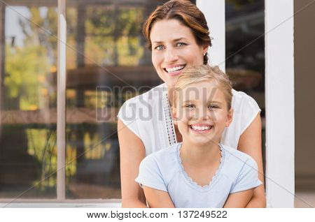 Mother and smiling daughter sitting outside the house. Happy mom and little girl enjoying in a summer day. Portrait of young mother embracing daughter sitting outside the house and looking at camera.