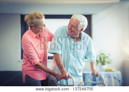 Happy senior woman helping senior man to walk with walker
