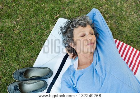 Smiling senior woman lying on mat at garden with eyes closed. High angle view of beautiful mature woman relaxing after yoga in park. Top view of senior woman sleeping at park.