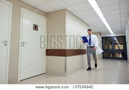 clinic, people, health care and medicine concept - doctor with clipboard walking along hospital corridor