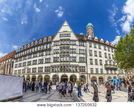 MUNICH GERMANY - MAY 27 2016: people in the pedestrian zone with view of Hirmer the largest men's fashion house in the world with decoration in Munich Germany