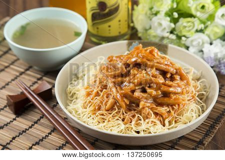 Traditional chinese bowl of rice vermicelli with minced fried pork on the table in restaurant
