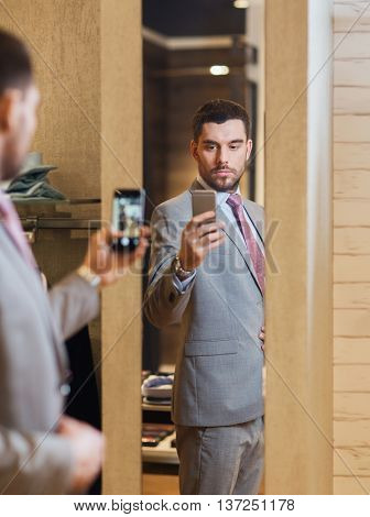 sale, shopping, fashion, style and people concept - young man in suit with smartphone taking mirror selfie at clothing store