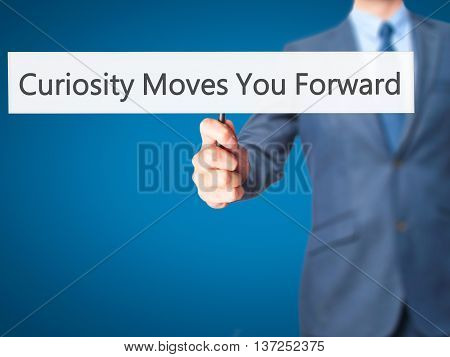 Curiosity Moves You Forward - Businessman Hand Holding Sign