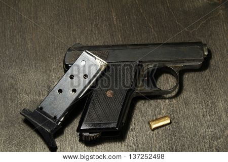 Metal Handgun With Ammo On Black Wooden Background