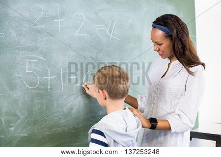 Smiling teacher assisting boy in doing addition on chalkboard in classroom at school