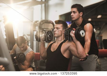 sport, fitness, lifestyle and people concept - group of men with dumbbells in gym
