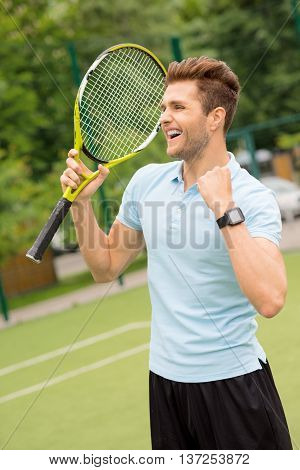 I won. Happy tennis player is celebrating his triumph. He is gesturing and laughing. Man is standing and carrying a racket