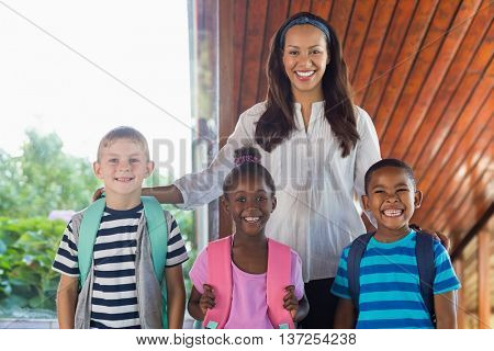 Portrait of smiling teacher and kids standing together with arm around at school