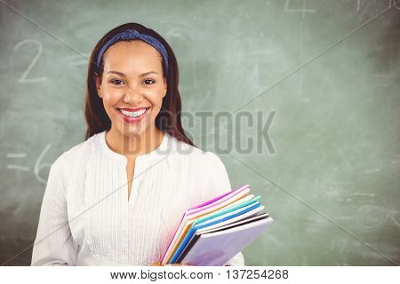 Portrait of smiling school teacher holding books in classroom at school