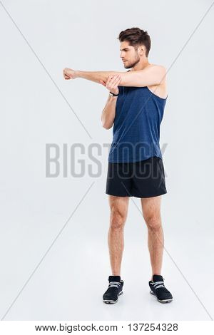 Handsome young sportsman stretching hands during workout isolated on a gray background