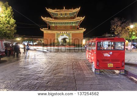 Heqing China - March 14 2016: Night view of the Pagoda in the city center of Heqing in Yunnan. This pagoda is the landmark if the city. Tourists and cars passing by nearby.