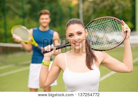 Cheerful two tennis players are enjoying the game. They are carrying rackets and smiling. Woman is looking at camera with happiness. Man is standing on background