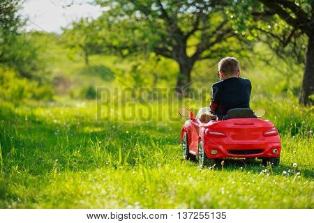 young man in the park against the backdrop of a red car